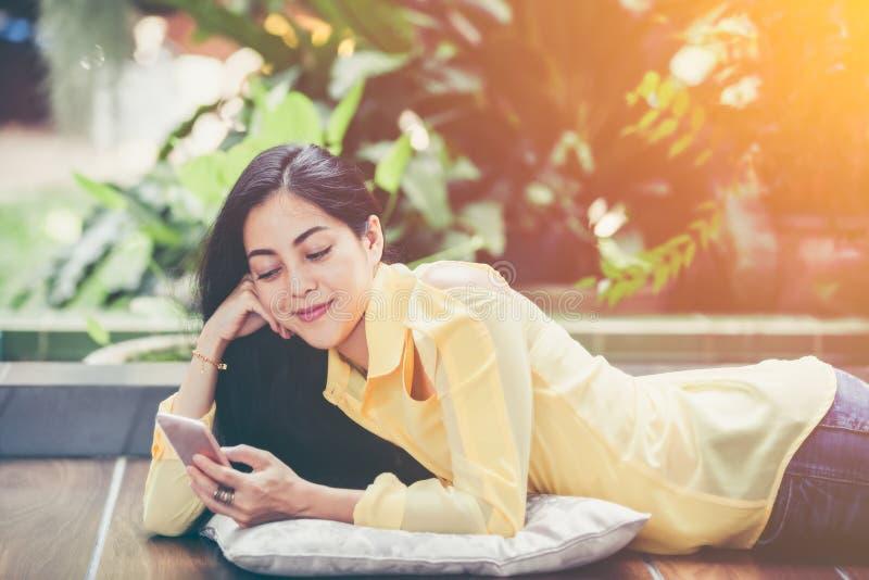 Gelukkige Aziatische vrouw die en slimme telefoon glimlachen met behulp van In openlucht op som stock foto
