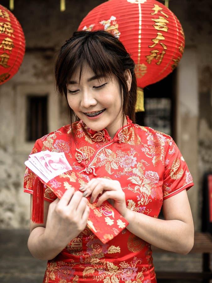 Gelukkige Aziatische vrouw die in traditionele Chinese kleding een rode zak met het Chinese gelukkige geld van honderd Yuansbankb stock afbeeldingen