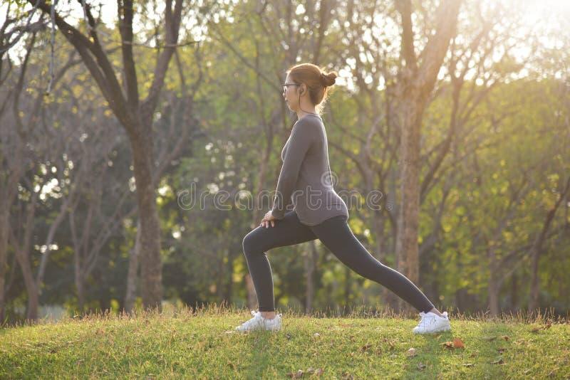 Gelukkige Aziatische vrouwelijke training bij het park stock foto