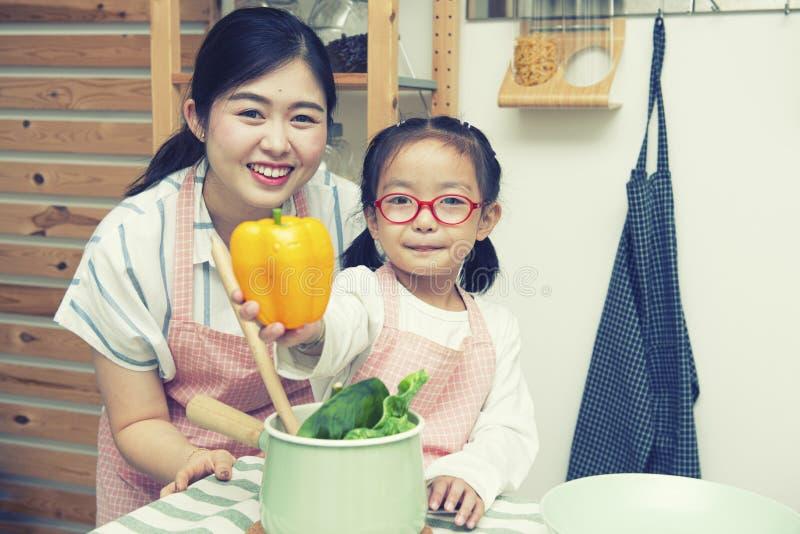 Gelukkige Aziatische vrouwenmamma en dochter in keuken, het gele capsicum van de meisjehand met gelukkig gezicht en glimlach royalty-vrije stock afbeelding