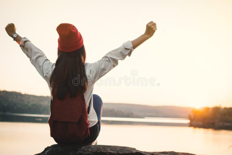 Gelukkige Aziatische vrouwenzitting op rots in aard tijdens zonsondergang stock afbeelding