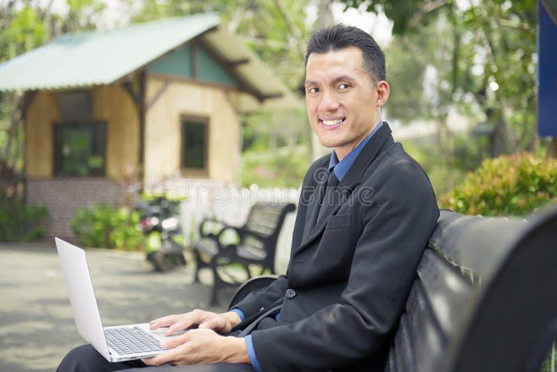 Gelukkige Aziatische zakenmanzitting en het gebruiken van laptop royalty-vrije stock afbeelding