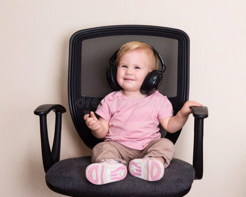 Gelukkige baby als bureauvoorzitter in hoofdtelefoons Peutermeisje het luisteren royalty-vrije stock afbeeldingen