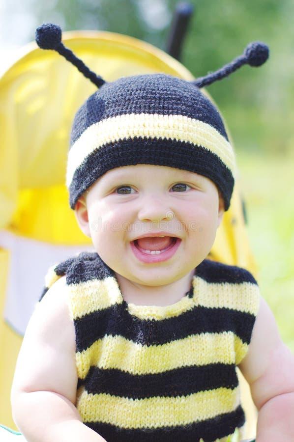 Gelukkige baby in de zitting van het bijenkostuum op kinderwagen stock afbeelding
