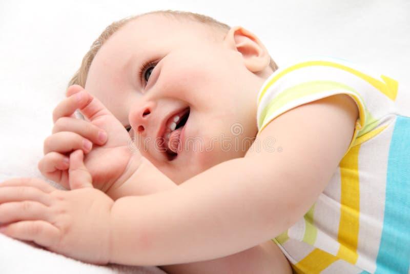 Gelukkige baby die in bed liggen stock afbeelding
