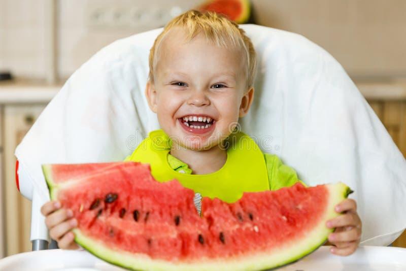 Gelukkige baby die een plak van een zoete heerlijke watermeloen eten Jong geitje het bijten van een stuk van watermeloen en het k stock foto's