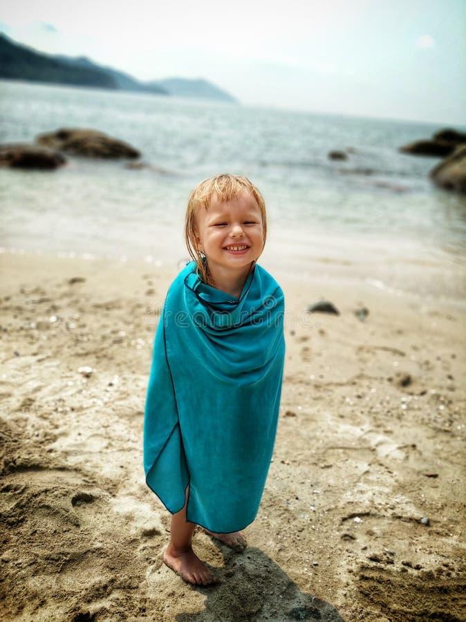 gelukkige baby die op de zandige oceaankust, nat in een blauwe handdoek lachen stock foto