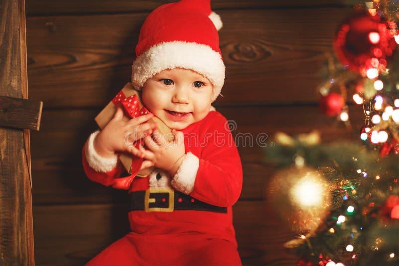 Gelukkige baby met gift bij Kerstmisboom stock afbeelding