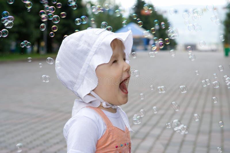 Gelukkige baby met zeepbels stock fotografie