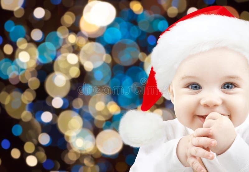Gelukkige baby in santahoed over Kerstmislichten stock afbeelding