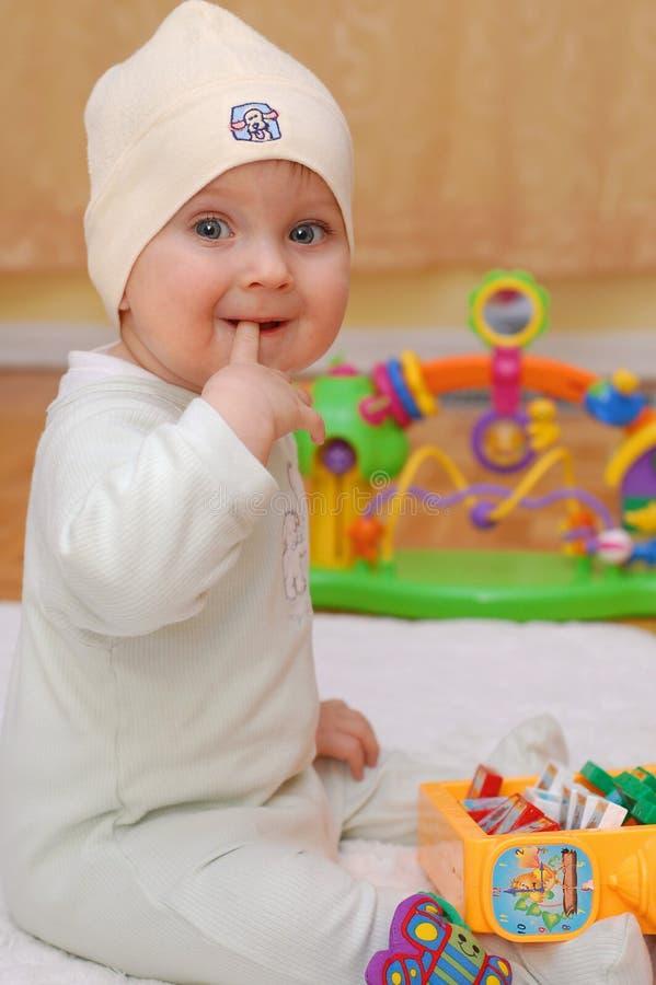 Gelukkige babyjongen die zijn vinger bijt stock afbeelding
