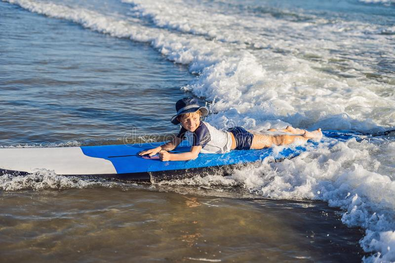 Gelukkige babyjongen - jonge surferrit op surfplank met pret op overzees stock fotografie