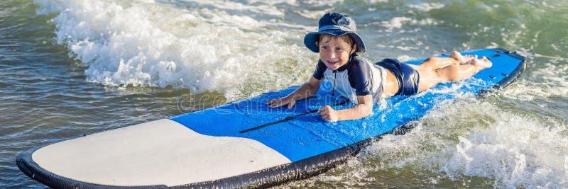 Gelukkige babyjongen - jonge surferrit op surfplank met pret op overzeese golven Actieve familielevensstijl, de sportlessen a van royalty-vrije stock foto's