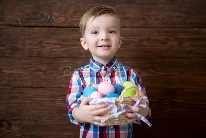 Gelukkige babyjongen met een mand van paaseieren op houten achtergrond stock afbeelding