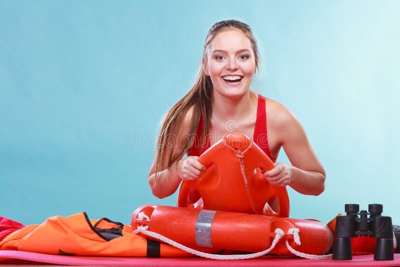 Gelukkige badmeestervrouw die op de boei van de reddingsring liggen stock foto's
