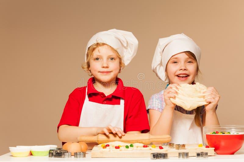 Gelukkige bakkers die deeg voor eigengemaakte koekjes maken stock foto's
