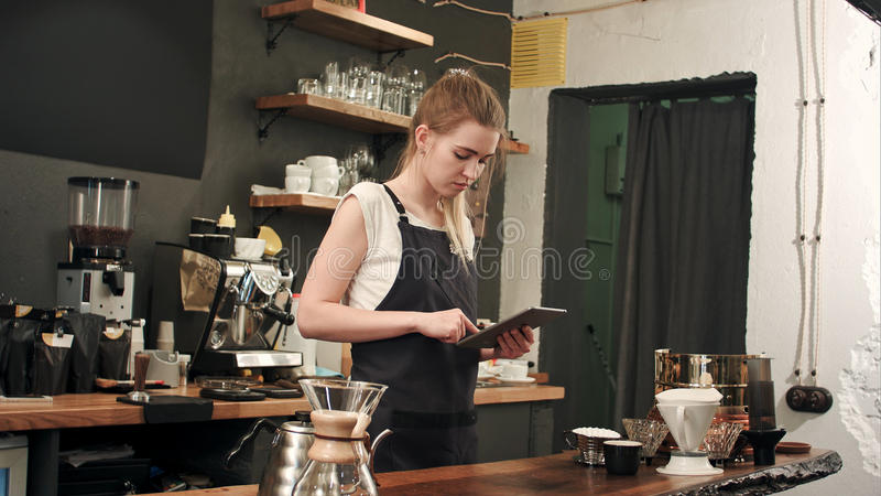 Gelukkige barista of de kelner in schort met de computer van tabletpc bij bar of koffie winkelt stock afbeeldingen