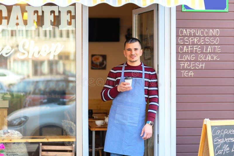 Gelukkige barista die zich bij koffieingang bevinden, portret van de rijpe bedrijfsmens woont nieuwe klanten in zijn coffewinkel  royalty-vrije stock fotografie