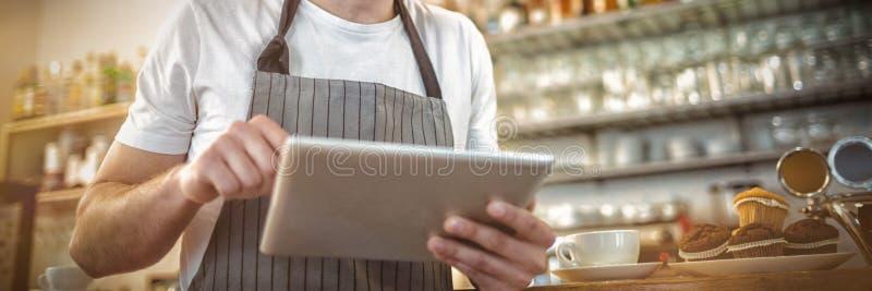 Gelukkige barista gebruikend digitale tablet bij koffie stock afbeeldingen