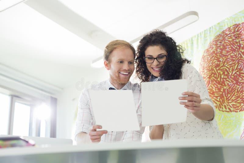 Gelukkige bedrijfscollega's die steekproeven in creatief bureau onderzoeken royalty-vrije stock afbeeldingen