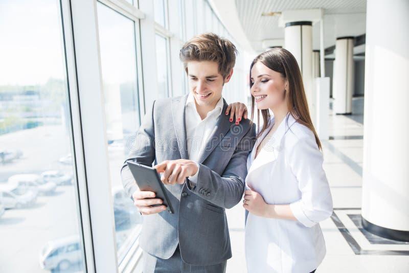 Gelukkige bedrijfscollega's in modern bureau die tablet gebruiken die nieuw project bespreken royalty-vrije stock afbeeldingen