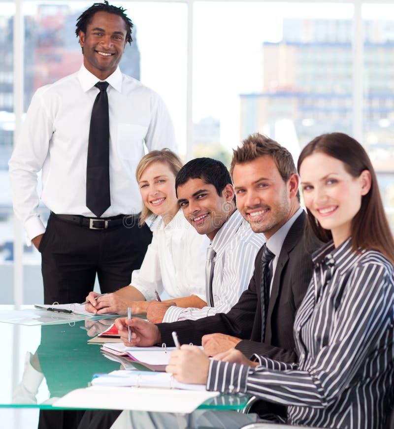 Gelukkige bedrijfsleider met zijn team in een vergadering royalty-vrije stock afbeelding
