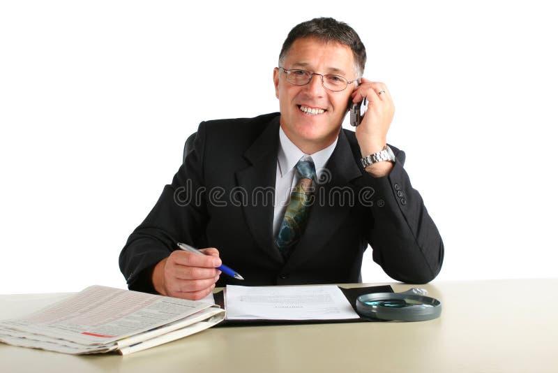 Gelukkige bedrijfsmens bezig op een telefoon die, die een contract ondertekenen en financieel nieuws lezen stock foto's