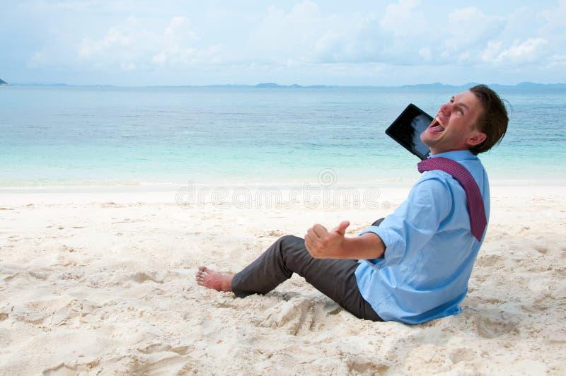 Gelukkige bedrijfsmens die aan het strand met PC werkt stock afbeelding