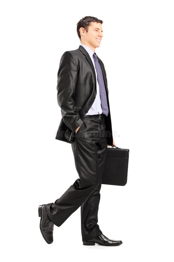 Gelukkige bedrijfsmens die een aktentas en het lopen houden stock foto