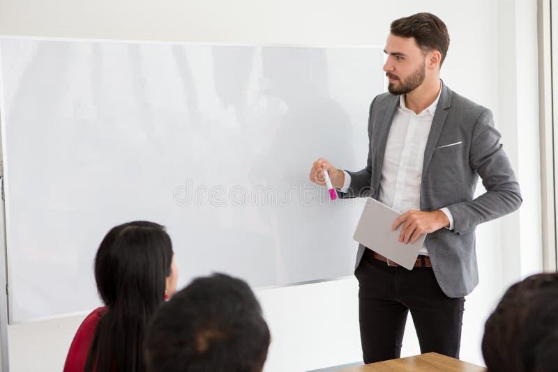 gelukkige bedrijfsmens die een presentatie op whiteboard maken chef- voorstellende strategie om aan doel van succes met binnen gr royalty-vrije stock foto's