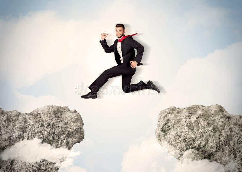 Gelukkige bedrijfsmens die over een klip springen stock foto