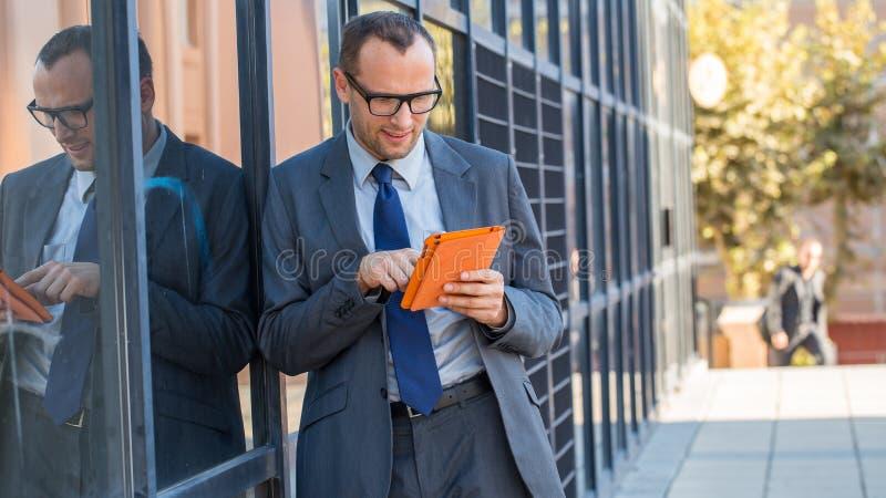 Gelukkige bedrijfsmens die tabletpc in oranje dekking op een stadsstreptokok met behulp van royalty-vrije stock foto's