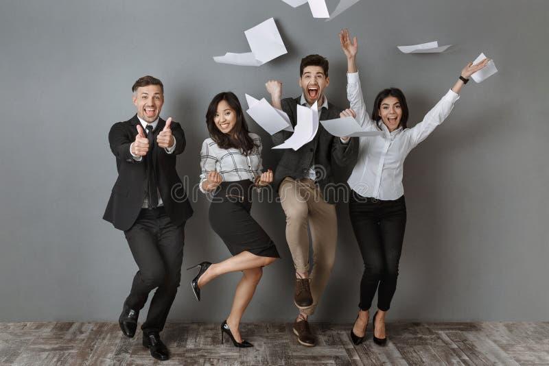 gelukkige bedrijfsmensen die tussen verschillende rassen zich bij grijze muur na succesvol bevinden stock fotografie