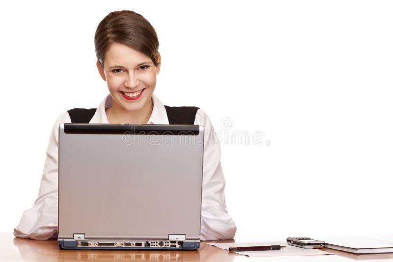 Gelukkige bedrijfsvrouw in de bureauwerken aangaande laptop stock fotografie