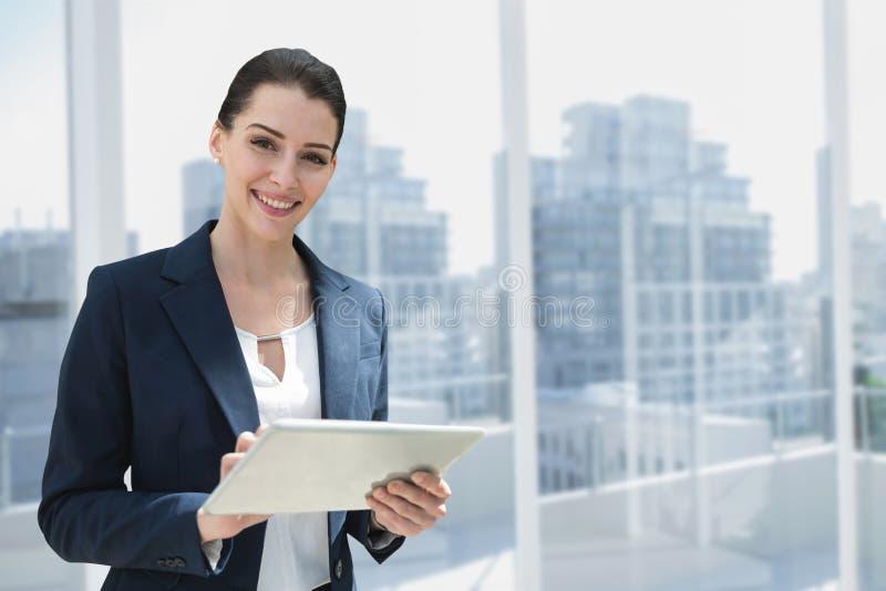 Gelukkige bedrijfsvrouw die een tablet gebruiken tegen stadsachtergrond royalty-vrije stock afbeelding
