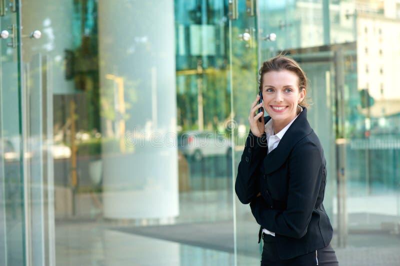 Gelukkige bedrijfsvrouw die en door celtelefoon lopen roepen stock foto's