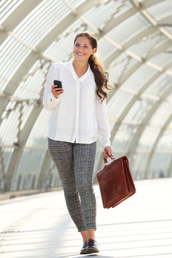 Gelukkige bedrijfsvrouw die met aktentas en cellphone lopen royalty-vrije stock foto's
