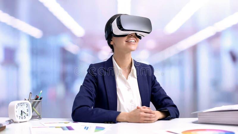 Gelukkige bedrijfsvrouw die in vrbeschermende brillen bureau zitten, cyber voorzien van een netwerk, toekomst stock foto