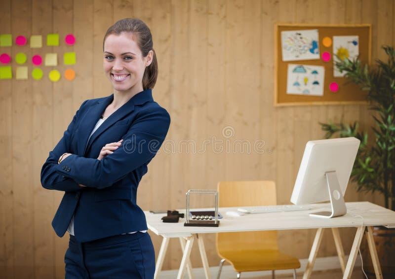 Gelukkige bedrijfsvrouw die zich tegen bureauachtergrond bevinden royalty-vrije stock afbeelding
