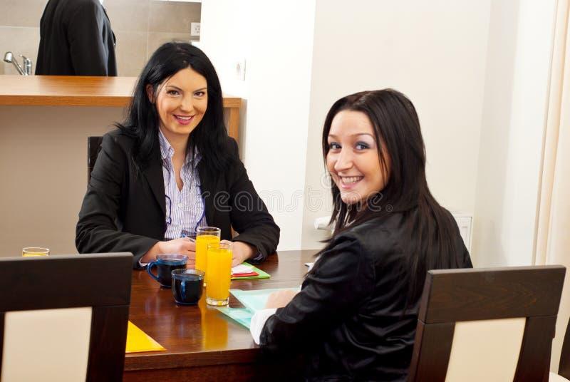Gelukkige bedrijfsvrouwen bij vergaderingslijst royalty-vrije stock foto