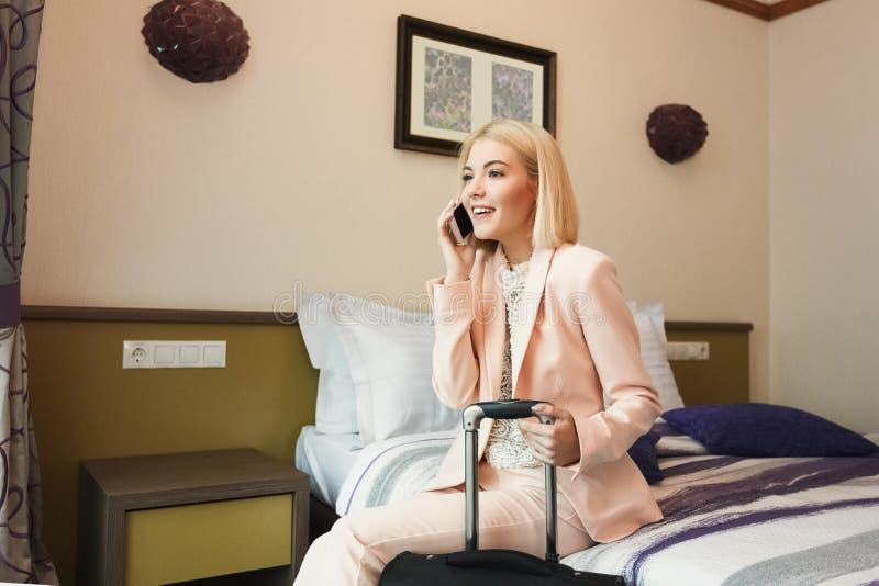 Gelukkige bedrijfsvrouwenzitting in hotelruimte royalty-vrije stock foto's