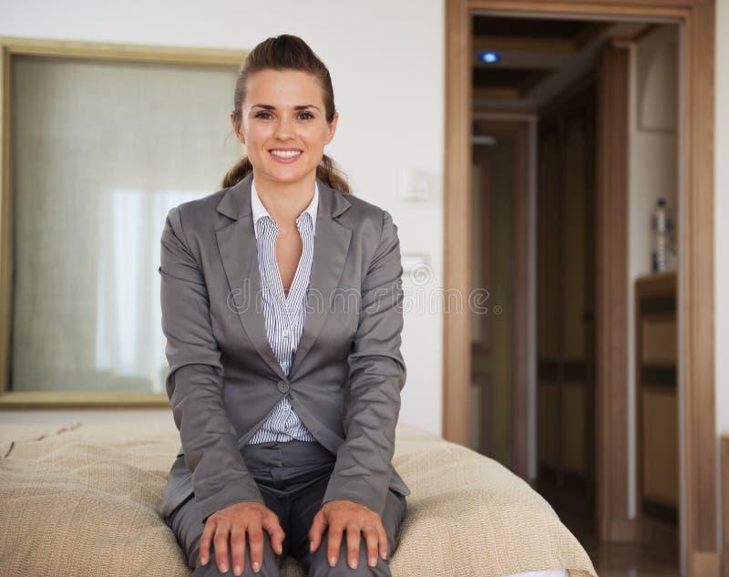 Gelukkige bedrijfsvrouwenzitting op bed in hotelruimte royalty-vrije stock fotografie