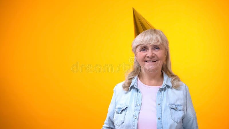Gelukkige bejaarde dame in partijhoed tegen gele achtergrond, verjaardagsviering stock foto