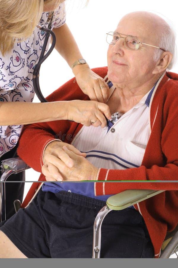 Gelukkige bejaarde die in rolstoel vitals controleert stock foto's