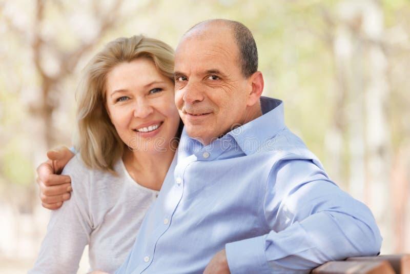 Gelukkige bejaarde en vrouw die op een bank koesteren stock foto