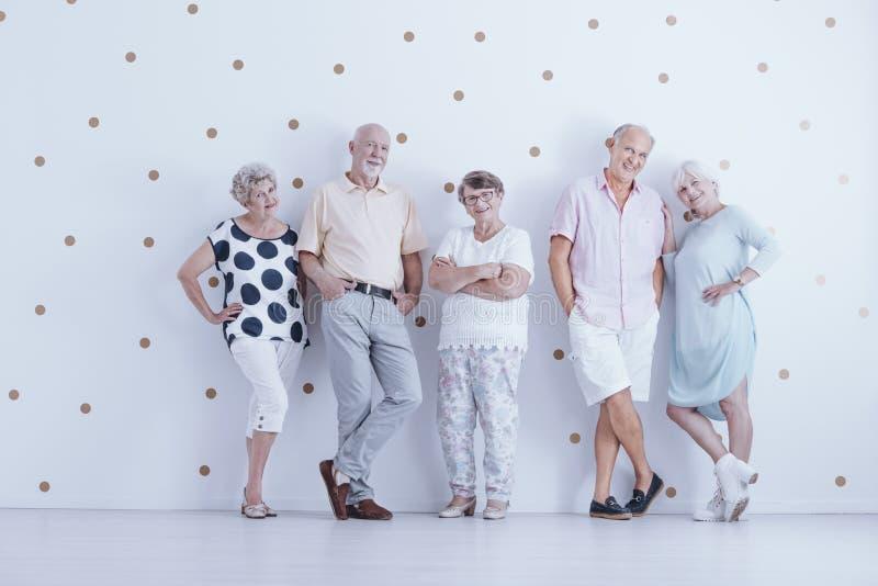 Gelukkige bejaarde mensen in vrijetijdskleding in witte studio met goud stock afbeeldingen