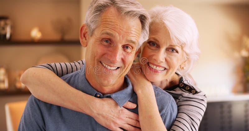 Gelukkige bejaarde paarzitting die thuis bij camera glimlachen stock afbeelding