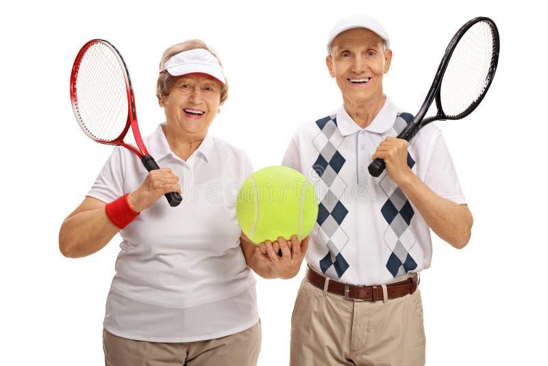 Gelukkige bejaarde tennisspelers die een grote tennisbal houden stock afbeelding