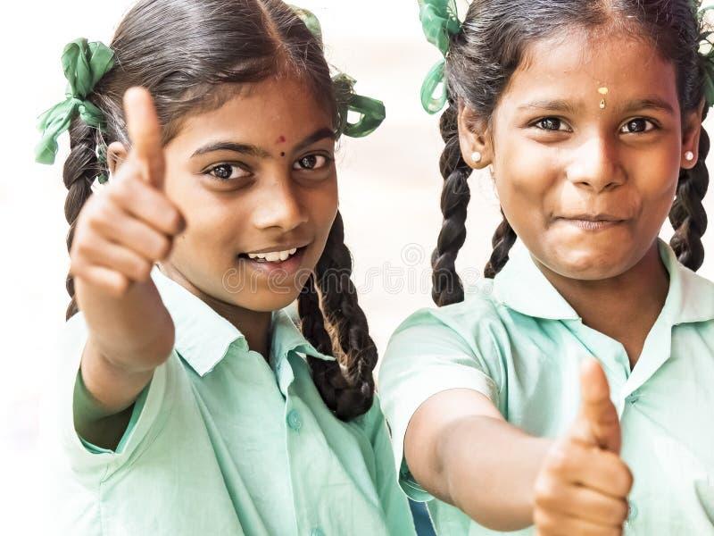 Gelukkige beste de meisjesklasgenoten die van kinderenvrienden tonend duim op gebaar op de school glimlachen Het multi-etnische s royalty-vrije stock fotografie