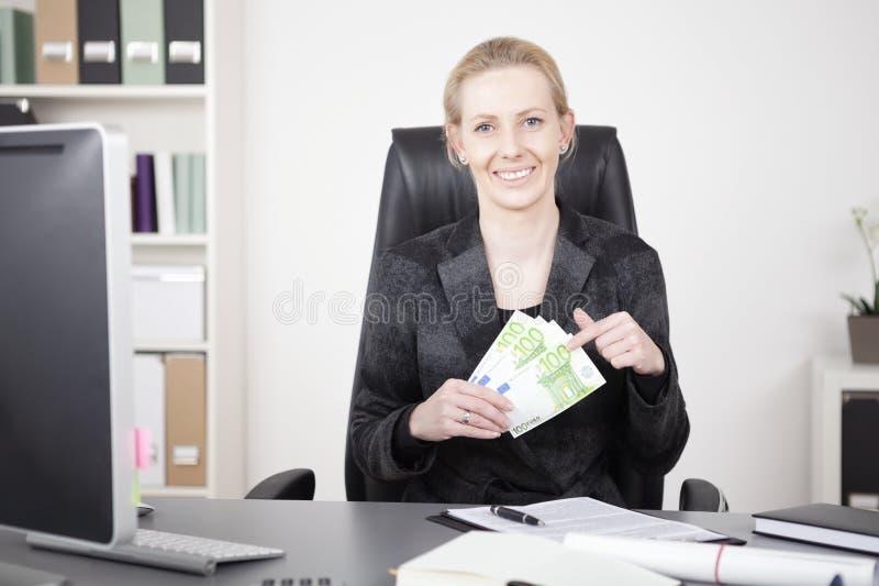 Gelukkige Bestuurster die bij haar Bureau een Ventilator van Contant geld houden royalty-vrije stock afbeelding